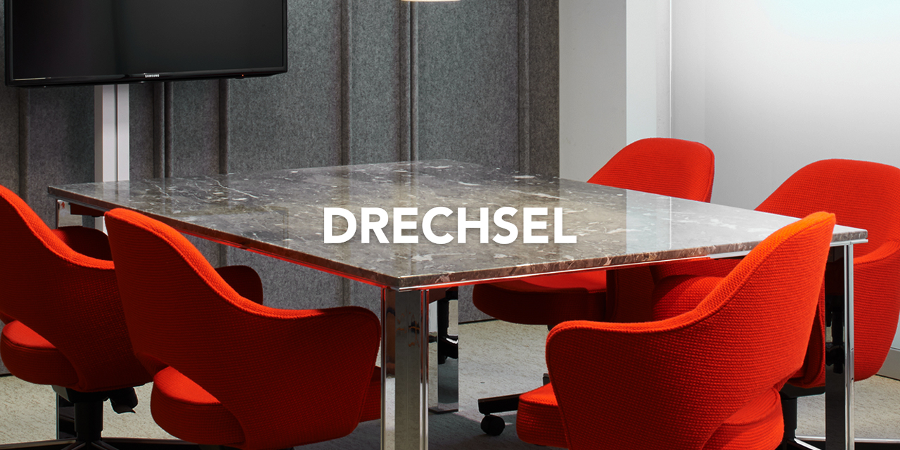 Conference room with burnt orange chairs and Drechsel Logo overlayed on top of it
