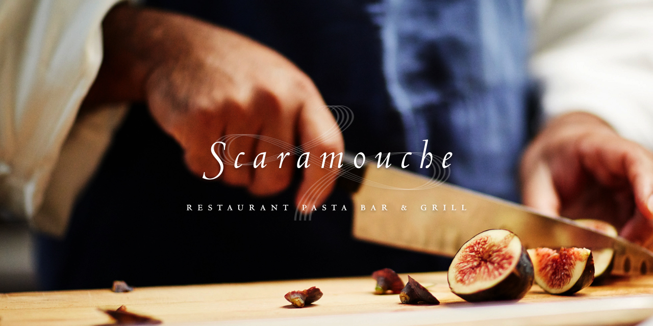 Chef cutting figs on a wooden cutting board with Scaramouche Logo overlayed on top of it