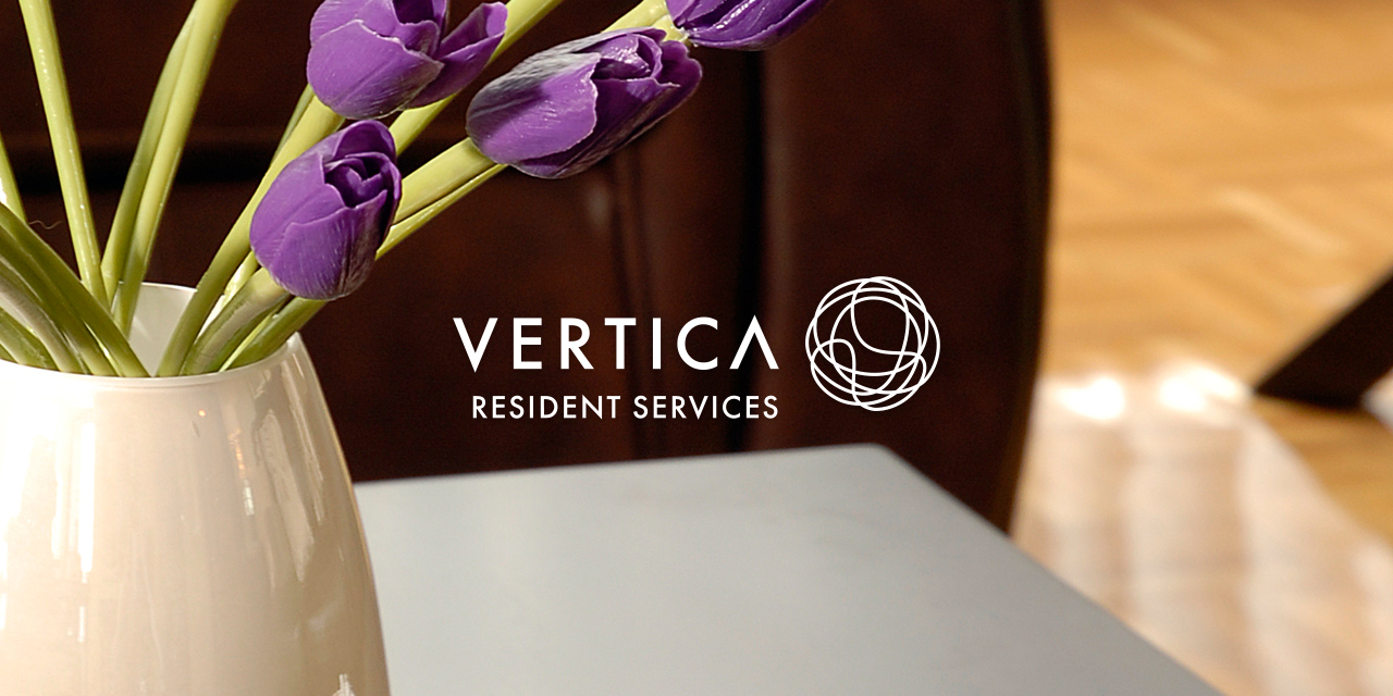 Table and purple tulips in a living space with the Vertica Resident Services Logo overlayed on top of it